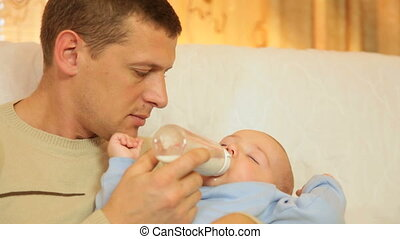 Young father feeding her baby boy milk formula from a bottle...
