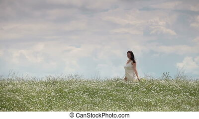 Pregnant young woman walking through chamomile field against sky in summer