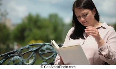 Pregnant young woman sitting on a park bench reading a book...