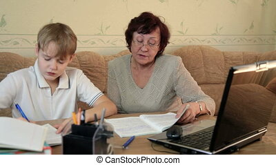 Grandma helping her grandson doing homework sitting at a...