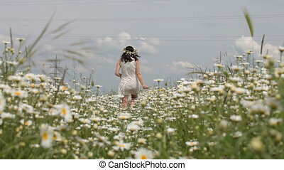 young pregnant woman leaving afar through the chamomile field in summer