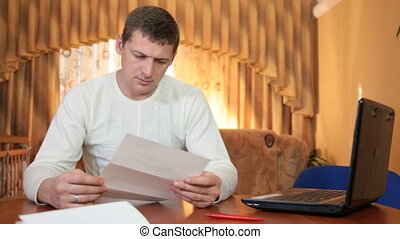 Frustrated young man reading some bad news in a letter at...