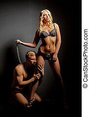 BDSM concept. Imperious mistress and submissive posing at...