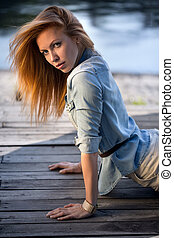 Red-haired girl with blue eyes lying on a wooden pavement...