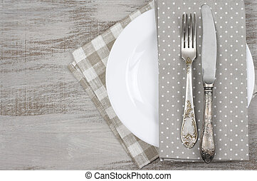 Table setting: white plate, vintage fork and knife with...