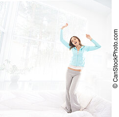 Beautiful and happy young woman jumping and stretching on...