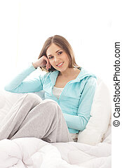 Young, attractive, happy woman sitting in the bed over white...