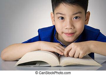Little asian boy read a book