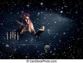 Beautiful witch making the witchcraft over the smoky...