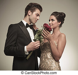 Husband offering his beautiful wife a bunch of red roses,...