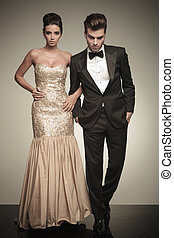 Full body picture of a elegant couple walking on studio...