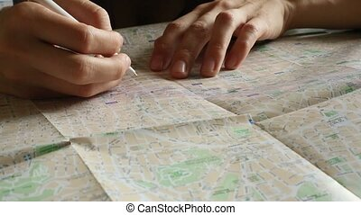Hand makes notes in pencil on map - Hand makes notes in...