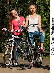 Two teenage girls with bicycle in a park on sunny day