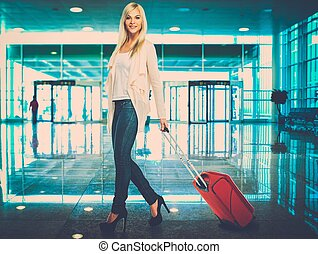 Blond woman with suitcase in airport - Blond woman with...