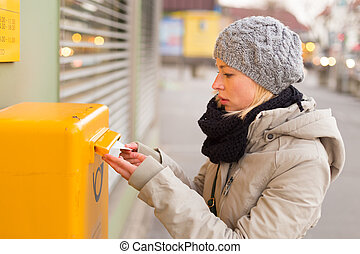 Young lady posting letters - Young woman posting a letter,...