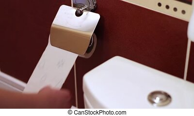 The unwinding of toilet paper - The man quickly unwind a...