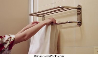 The man hangs up towels on the rack - Girl hanging white...