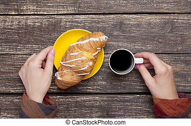 Female holding cup of coffee and croissant