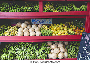 Pineapples and other fruits for sale at a roadside stand on...