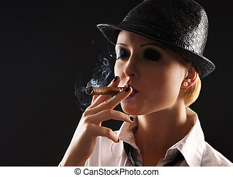 Young attractive female gangster smoking cigar over dark...