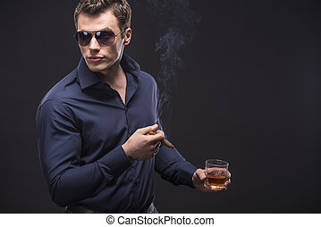 Fashion man - Young man in glasses is smoking a cigarette...