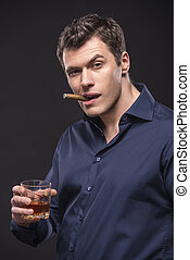 Fashion man - Young man is smoking a cigarette and is...