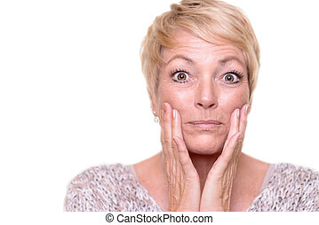 Attractive senior blond woman checking her complexion -...