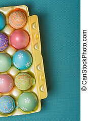 Box with painted easter eggs on blue background top view