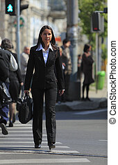 Young businesswoman crossing the street in a city.