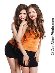 Two attractive girls with long wvy hair and makeup wearing...