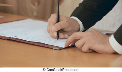 The groom signs in the book during a wedding ceremony in a registry office