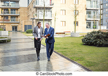 Two business people walking and discussing outside the...