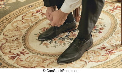 The groom puting shoes on and ties shoelaces - The groom...