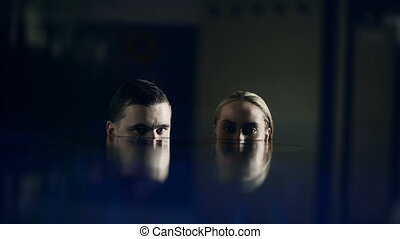 Dark Water - Couple with their faces half in water turning...