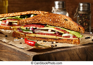 Two pieces of club sandwich on old papper with big cutting...