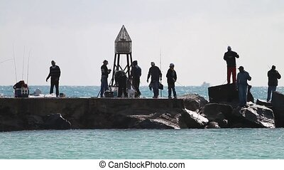 Fishermen fishing of a jetty - A group of fishermen on a...