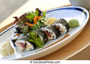 Maki and green salad on a plate