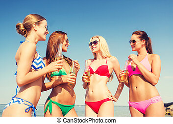 group of smiling young women drinking on beach - summer...
