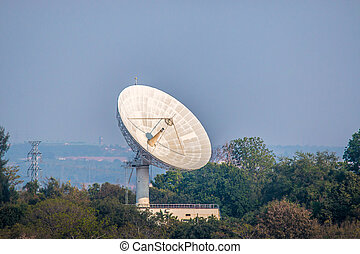 Large satellite dish on the forest over clouded background