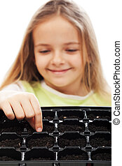 Little girl planting putting seeds into germination tray -...