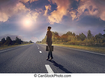 Road to success - Young businesswoman standing on road and...