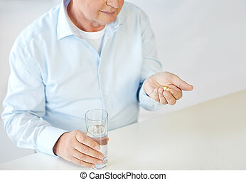 close up of old man with pills and water glass - oldness,...