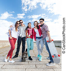 teenagers with skates outside - summer holidays and teenage...