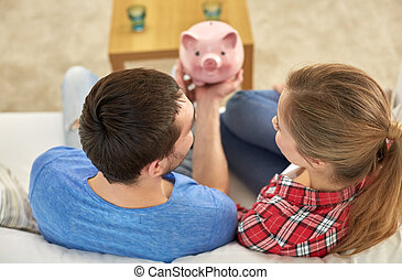 close up of couple with piggy bank sitting on sofa - money,...