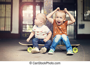 Little boy - Cute little boys sitting on a skateboard on...