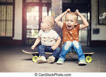 Little boy - Cute little boys sitting on a skateboard on...