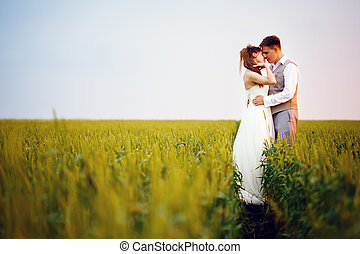 Happy young wedding couple kissing at the sunset in...