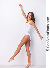 Walking beauty. Full length of attractive young brown hair woman in tank top and panties posing against white background and smiling