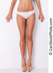 Perfect legs. Close-up of woman with beautiful legs leaning at the white wall