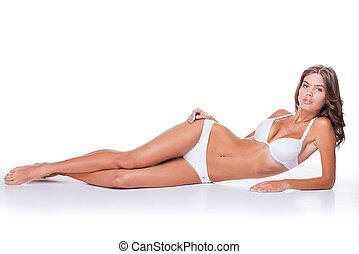 Beauty with perfect body. Attractive young brown hair woman in white lingerie lying against white background